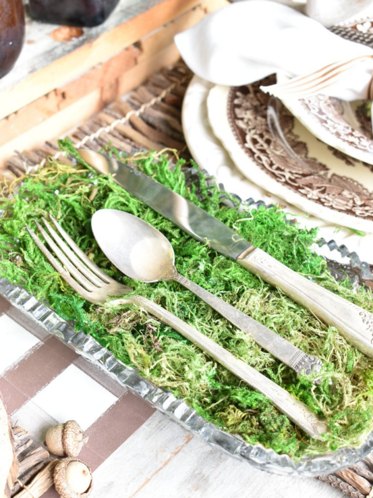 clear glass tray lined with green moss with spoon fork knife laying on top sitting beside place setting