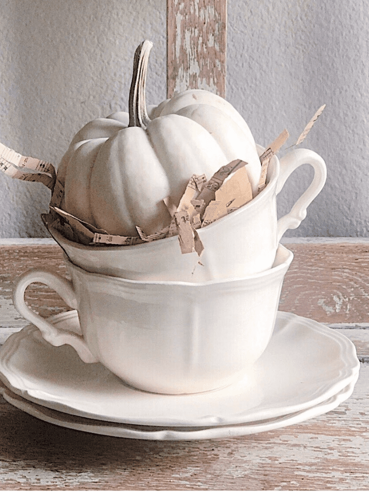 stack of white teacups on 2 saucers with a mini white pumpkin sitting in the top