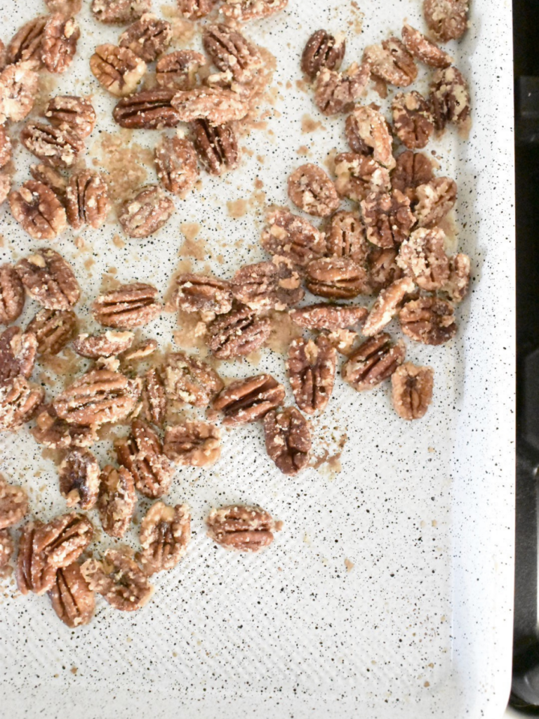 pecan halves coated in sugar laying on a white baking sheet