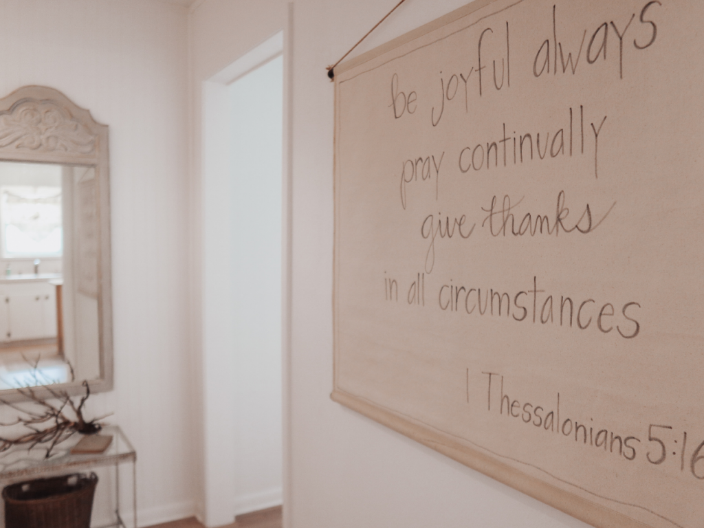 canvas wall hanging with 1 Thessalonians 5:16 scripture hand written in gray fabric pen