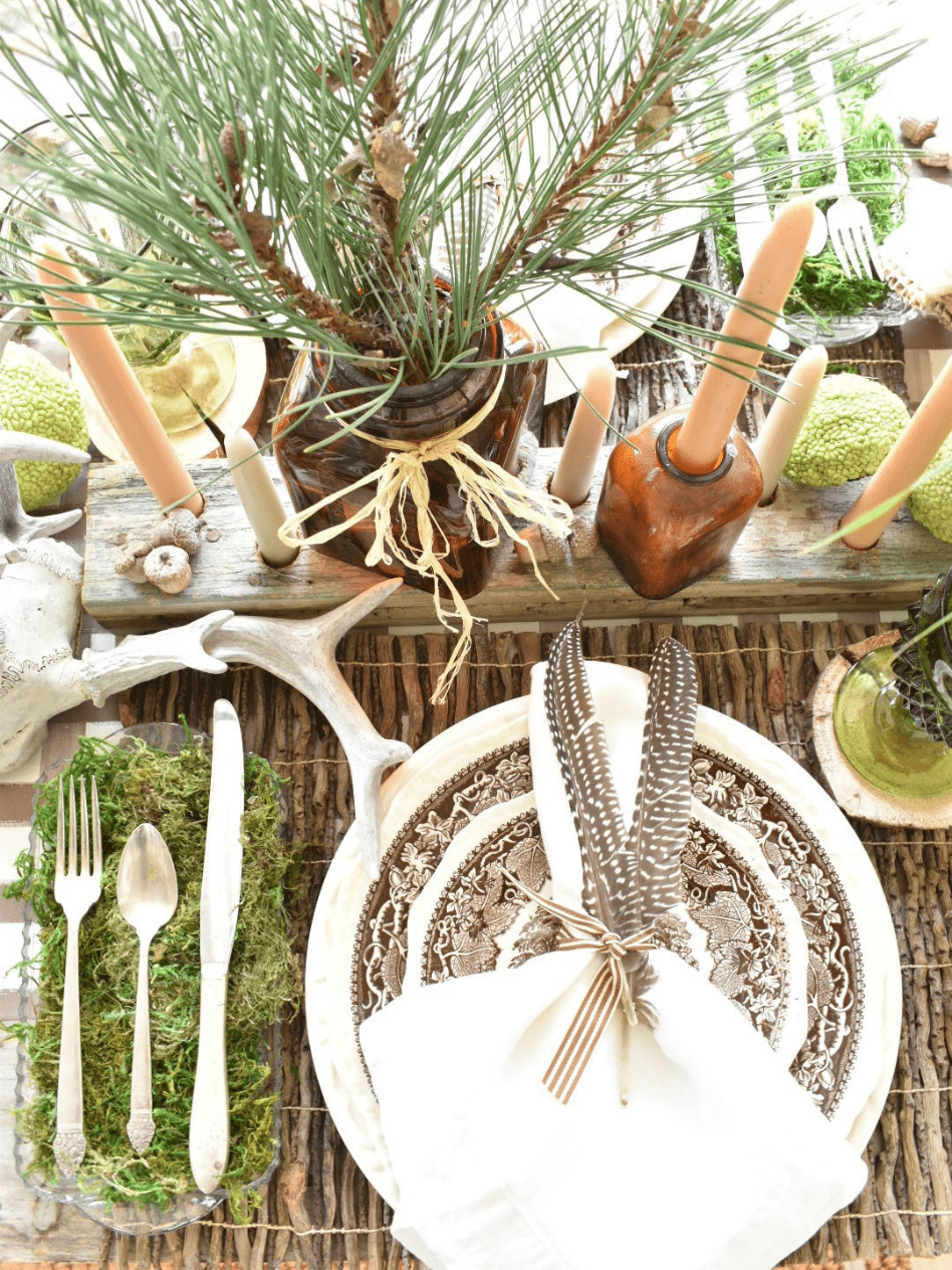 woodsy theme place setting with brown paper plaid tablerunner twig placemat brown transferware dinner plate with brown transferware salad plate on top white linen napkin with 2 feathers on top silverware in a tray lined with green moss to the left of the place setting amber vases with pine branches for centerpiece amber bottles with tapers for centerpiece antlers acorns and horse applesfor table