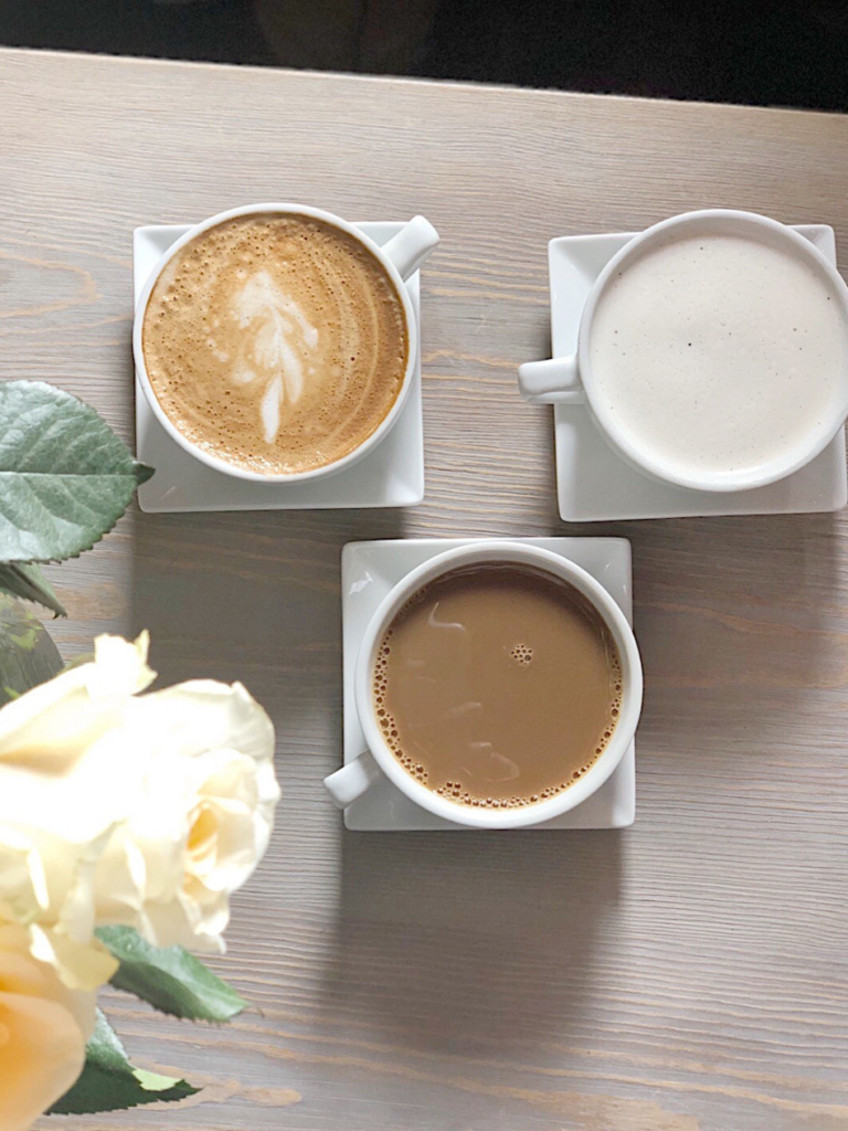 overhead shot of 3 cups coffee white mugs on white square saucers on light wood talbe yellow rose edgei n pic