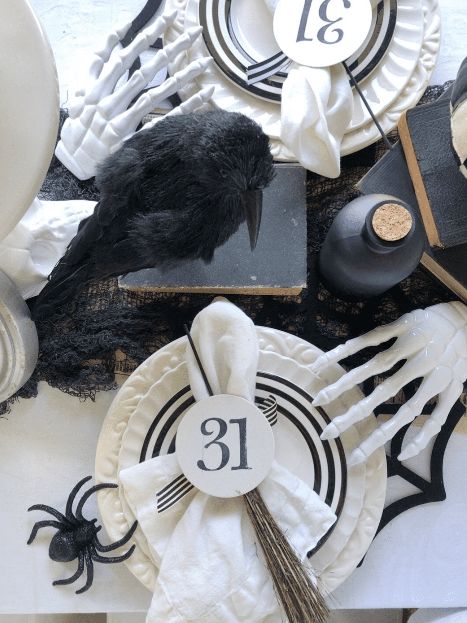 halloween place setting with 2 stacked white plates white salad plate with black stripe border on top of stack white napkin on top of plate with a round card with 31 stamped on it white skeleton hand on edge of plate black felt spider web placemat black crow on top of stack of black books