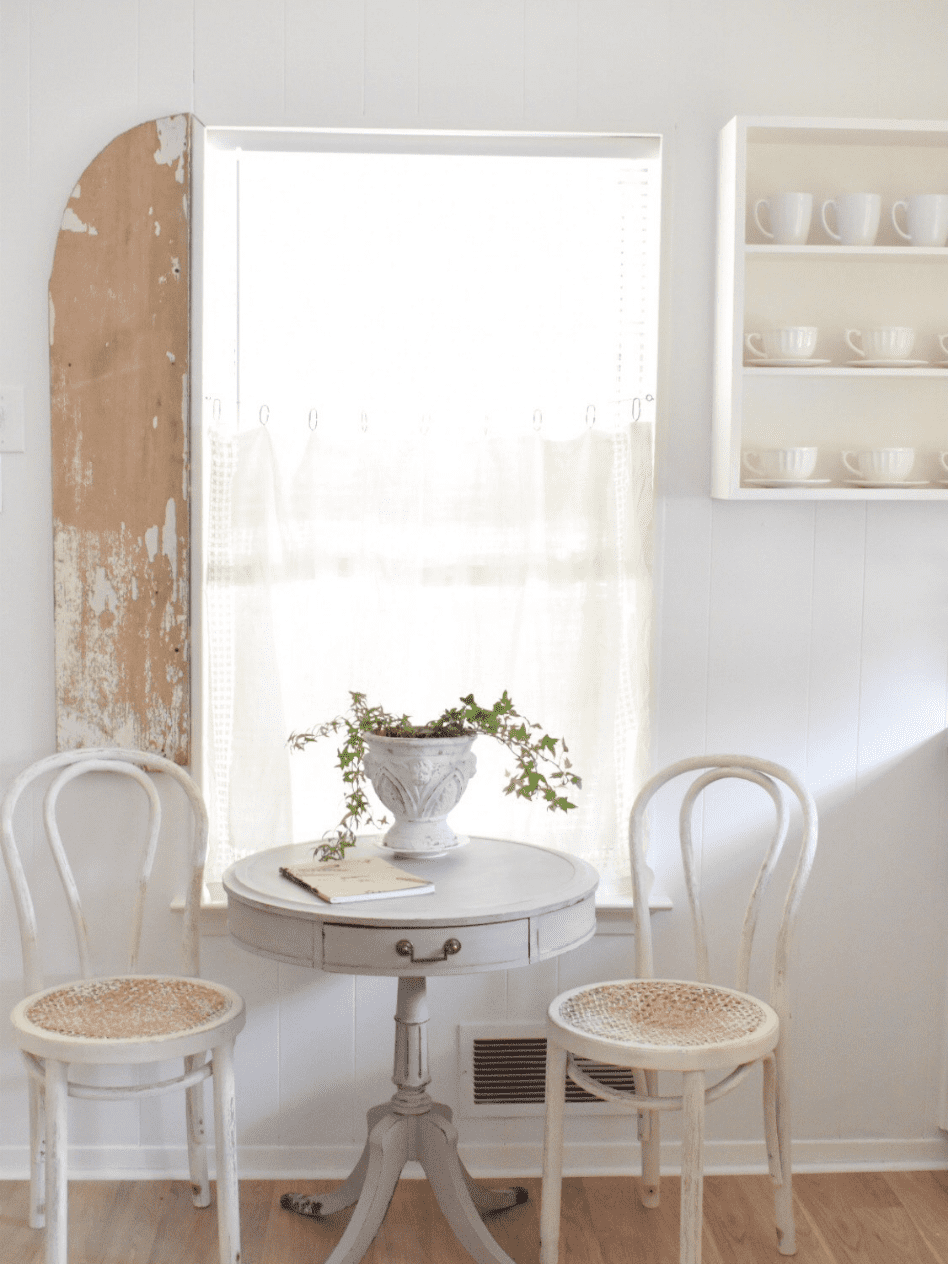 sitting area in kitchen white paneling walls white open shelves with coffee mugs small gray table with 2 can chairs plant in urn on table