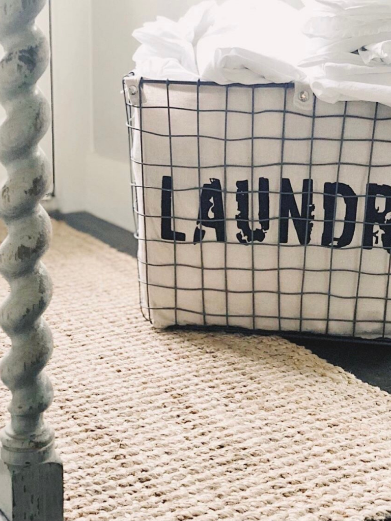 wire basket with liner that says LAUNDRY on jute rug