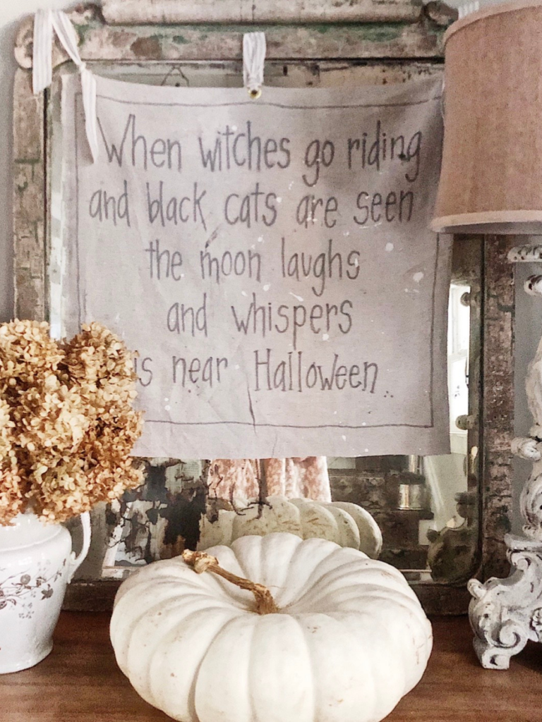 witch saying on drop cloth with black fabric marker writing hanging on vintage mirror white heirloom pumpkin on dresser in front of sign.